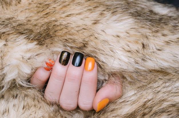 オレンジと黒のネイルアートと美しい女性の手 Premium写真