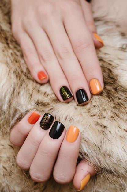オレンジと黒のネイルアートと美しい女性の手。 Premium写真