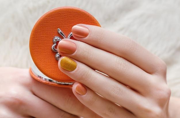 オレンジ色のネイルデザインと美しい女性の手。 Premium写真