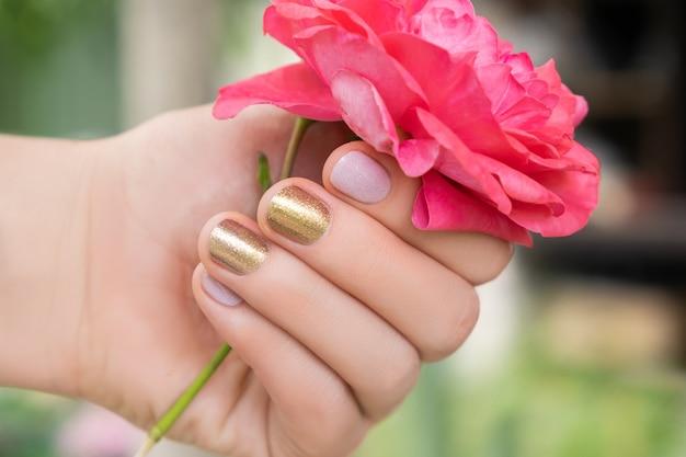 Красивая женская рука с идеальным золотым и розовым дизайном ногтя держит свежий цветок розы Бесплатные Фотографии