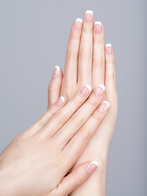 Beautiful female hands with french manicure on nails Free Photo