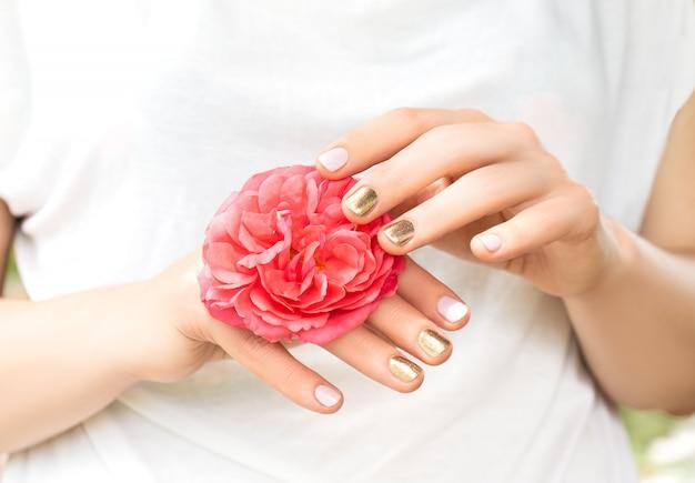 完璧な黄金とピンクのネイルデザインの美しい女性の手は、新鮮なバラの花を保持します 無料写真