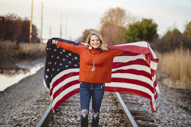 鉄道に立っている間アメリカの国旗を保持している美しい女性 無料写真