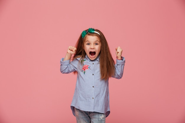 Beautiful female kid in hair hoop and fashion clothes clenching fists shouting with happiness and admiration Free Photo