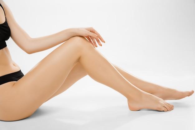 美しい女性の脚と白い背景で隔離の腹。美容、化粧品、スパ、脱毛、治療、フィットネスの概念。 無料写真