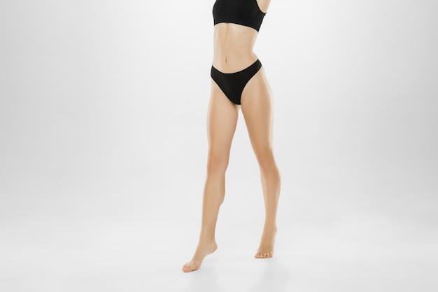 Bellissimi piedini femminili e pancia isolati su priorità bassa bianca. concetto di bellezza, cosmetici, spa, depilazione, trattamento e fitness. Foto Gratuite