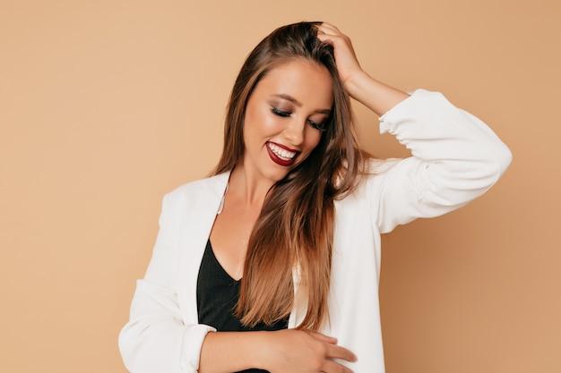 長い茶色の髪とつるの唇が素敵な笑顔で孤立した壁でポーズ美しい女性モデル。完璧な肌のクローズアップと手入れの行き届いた少女の肖像画 無料写真
