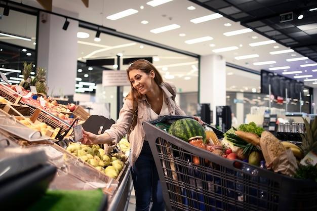 식료품 점에서 과일의 가격을 확인하는 아름다운 여성 사람 무료 사진