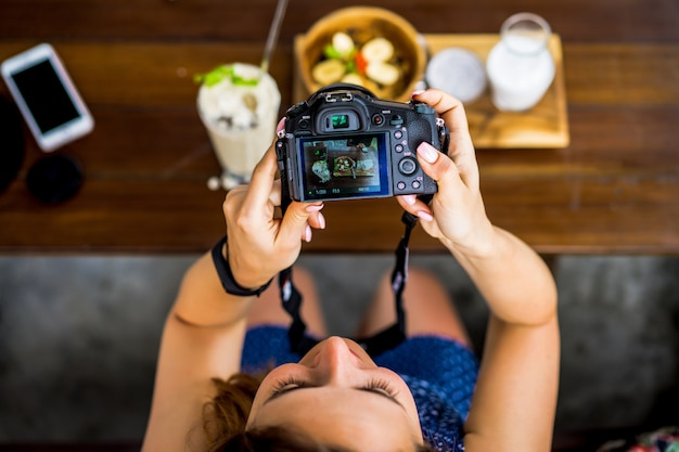Beautiful female photographs her food on camera. Premium Photo