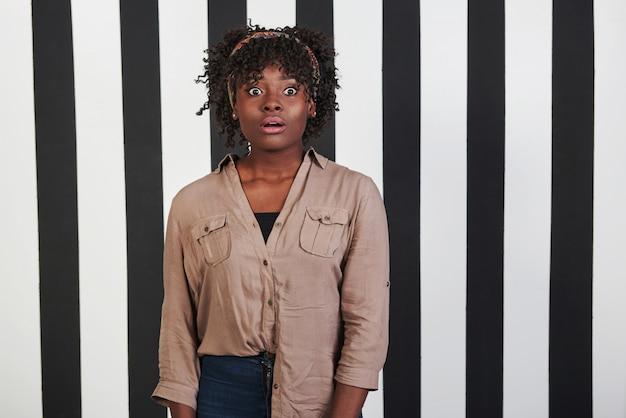 黒と青のストライプの背景に美しい女性の肖像画。アフリカ系アメリカ人の女の子はショックを受けた顔になります 無料写真