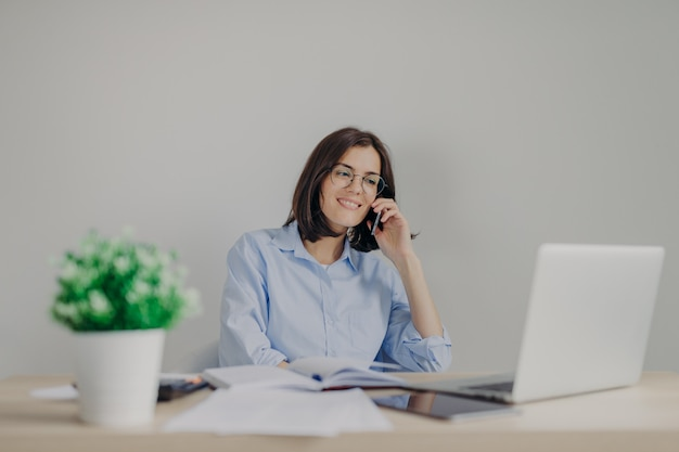 Beautiful female recruiter makes job offer to somene via cell phone, checks curriculum vitae on laptop computer Premium Photo