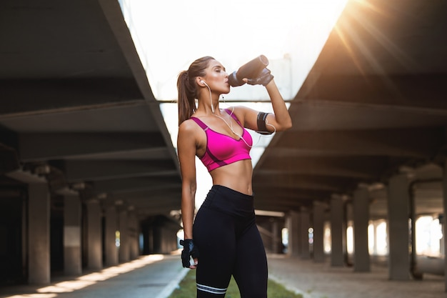 Beautiful female runner standing outdoors drinking water from her bottle. Premium Photo