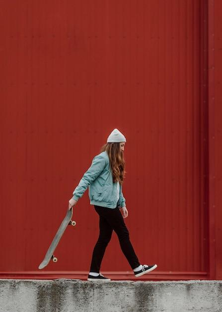 Bello pattinatore femminile che tiene il suo skateboard Foto Gratuite