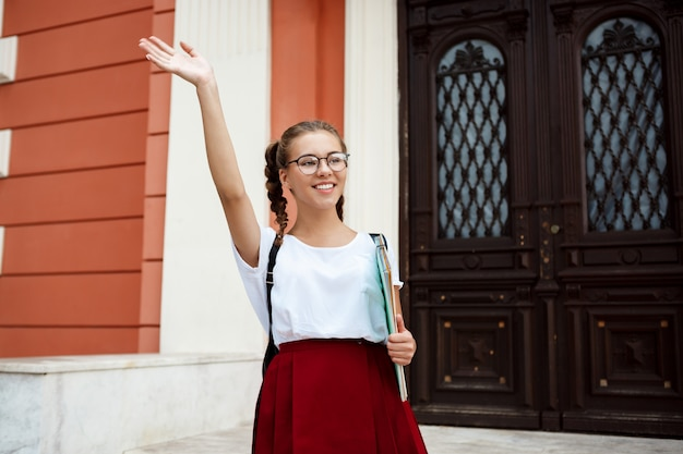 Красивая студентка в очках, улыбаясь, приветствие, держа папки на открытом воздухе Бесплатные Фотографии