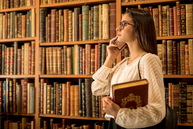 Beautiful female student with books speaking on phone in library Free Photo