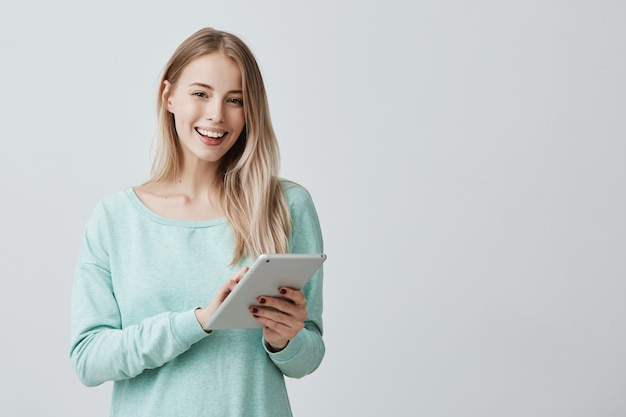 교육 또는 비즈니스 차트의 편집에서 작업에 대 한 태블릿을 사용 하여 긴 금발 머리를 가진 아름 다운 여성. 무료 사진