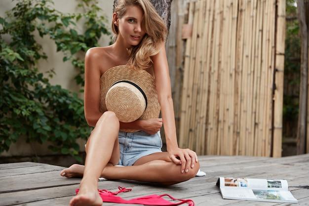 神秘的な表情の美しい女性。デニムのショートパンツを着て、ビキニを脱いで、麦わら帽子で裸の体を隠し、木の床に座って、雑誌を読み、レクリエーションの時間を楽しんでいます。レジャーとライフスタイル 無料写真