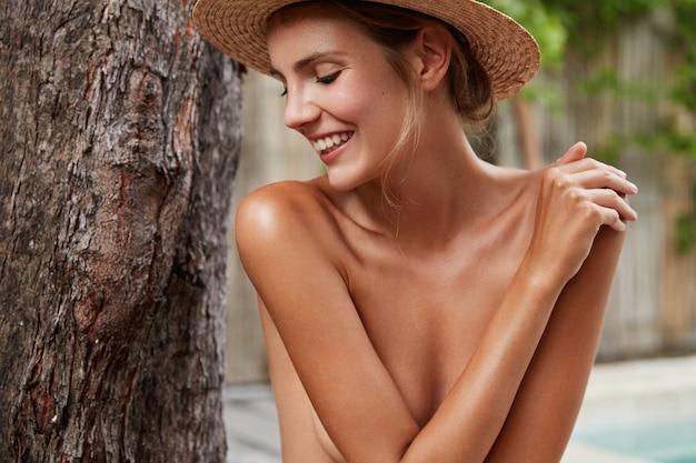 日焼けした健康的な純粋な肌を持つ美しい女性は、トロピカルビューに対してヌードをポーズし、目をそらし、前向きな笑顔を持ち、写真を撮られることをうれしく思い、完璧な体型をしています。美容とスキンケア 無料写真