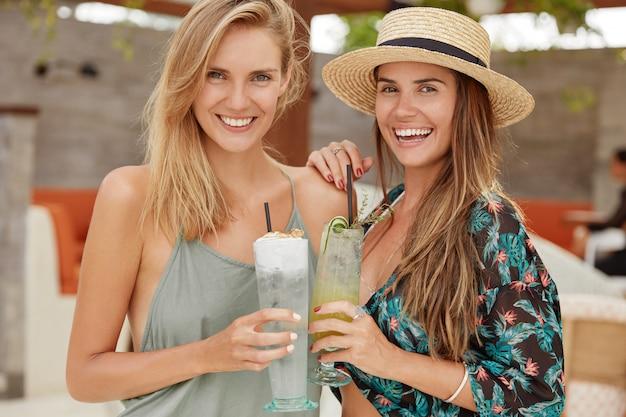 Красивые девушки стоят рядом, выглядят позитивно, отдыхают на морском курорте, держат свежие вкусные коктейли, обнимаются. гомосексуальная пара женского пола любит проводить свободное время в баре в отеле. Бесплатные Фотографии