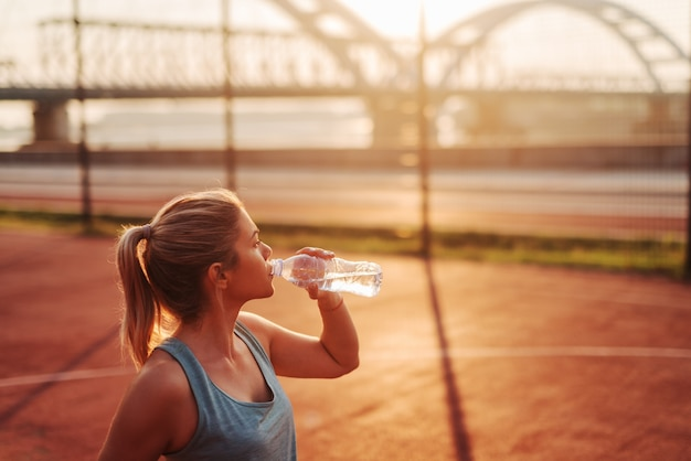 Beautiful fit sporty girl drinking water after hard early morning training. training outside and looking away . Premium Photo