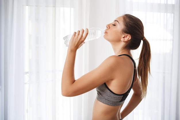 Beautiful fitness girl  drinking water from a plastic bottle Free Photo