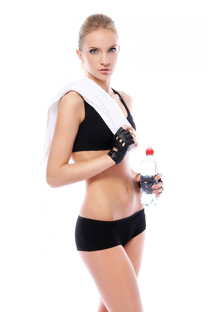 Beautiful fitness girl with towel and bottle of water Free Photo