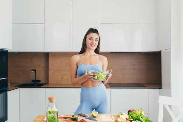 Красивая женщина фитнеса, готовит здоровую пищу дома Premium Фотографии