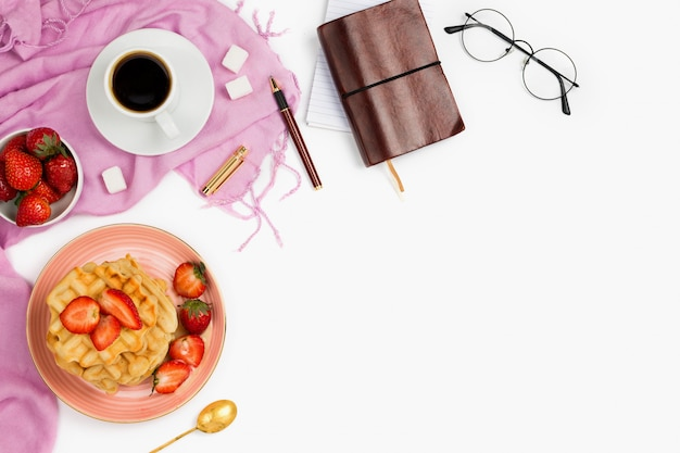 Beautiful flatlay arrangement with cup of coffee, hot waffles with cream and strawberries, glasses and other business accessories: concept of busy morning breakfast, white background. Premium Photo