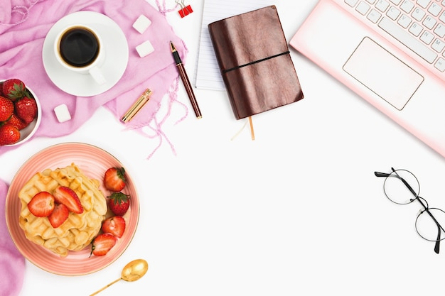 Beautiful flatlay arrangement with cup of coffee, hot waffles with cream and strawberries, laptop and other business accessories: concept of busy morning breakfast, white background. Premium Photo