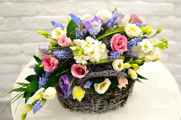 Красивая цветочная корзина на столе. красивый букет из разноцветных цветов Premium Фотографии