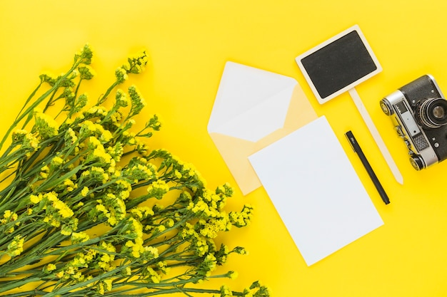 Beautiful flower bouquet; card; envelope; pen; camera and placard on yellow background Free Photo
