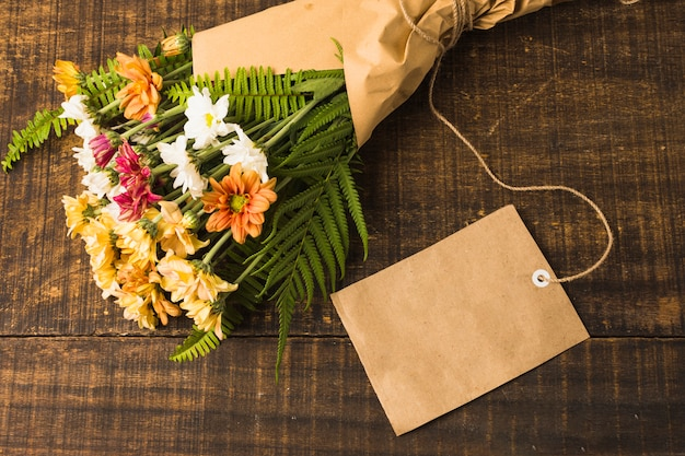 Beautiful flower bouquet with blank label over wooden desk Free Photo