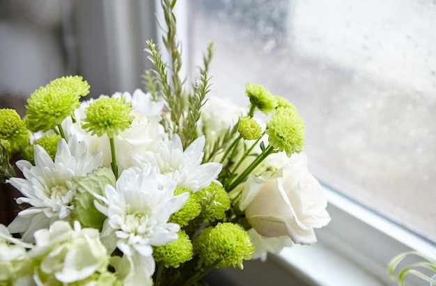 Bellissima composizione floreale con fiori bianchi e verdi vicino alla finestra Foto Gratuite