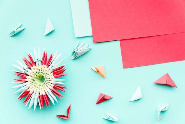 Beautiful flower origami made with red paper on teal backdrop Free Photo