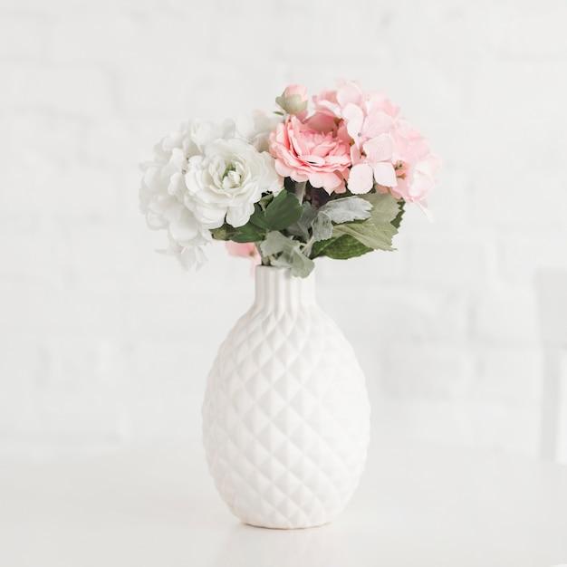 白いテーブルの美しい開花の花瓶 Premium写真