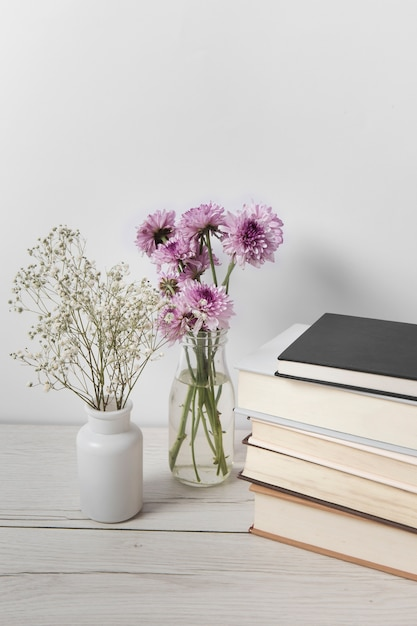 Beautiful flowers next to book pile Free Photo