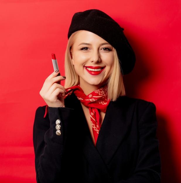 赤い壁に口紅のベレー帽で美しいフランス人女性 Premium写真