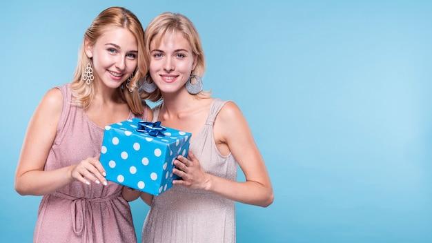 Beautiful friends holding gift box Free Photo