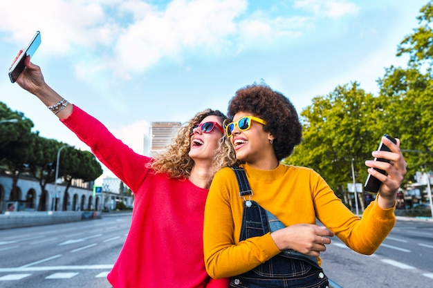 Beautiful friends taking a selfie in the street. communication concept Premium Photo