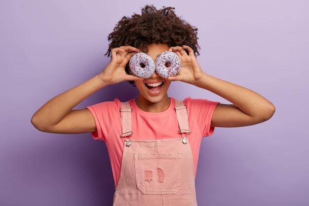 美しい面白いアフロアメリカ人女性は目に甘い紫色のドーナツを保ち、おいしいデザートで屋内で楽しんで、ピンクの服を着て、紫色の背景の上に隔離されています。ダイエット、ジャンクフード、減量の概念 無料写真