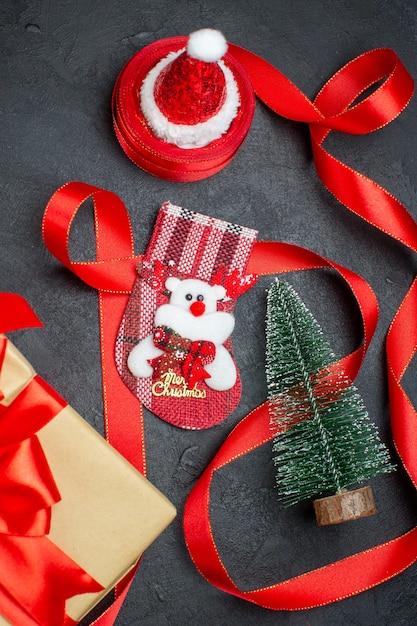 어두운 배경에 아름 다운 선물 크리스마스 양말 크리스마스 트리 산타 클로스 모자 무료 사진