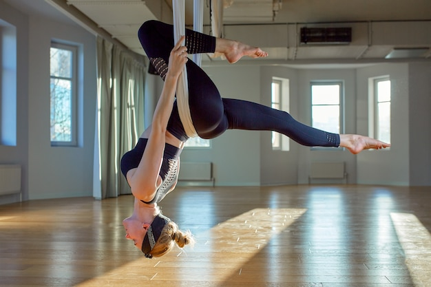 Beautiful girl aerial yoga trainer shows medutiruet on hanging lines upside down in a yoga room. concept yoga, flexible body, healthy lifestyle, fitness. Premium Photo
