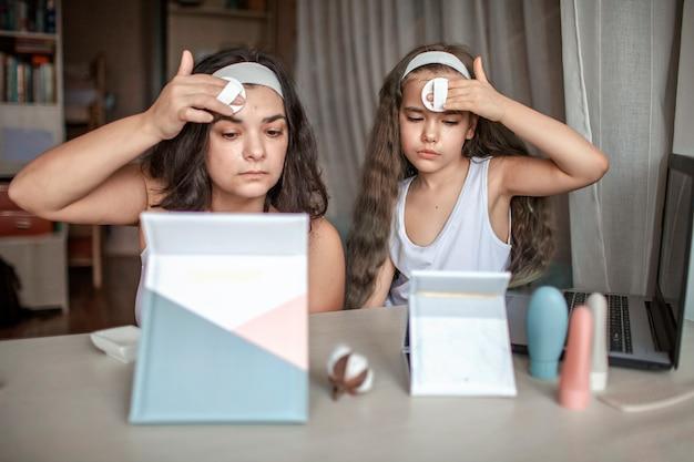 オンラインでタブレットで美容マスタークラスを見て、自分でスパの手順をしている美しい少女と彼女の母親、顔に滑らかなマスクを楽しんでいるママと娘、自宅の美容院 Premium写真