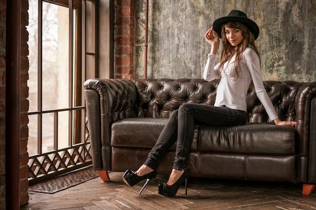 Beautiful girl in black hat sitting on sofa , stylish woman Premium Photo