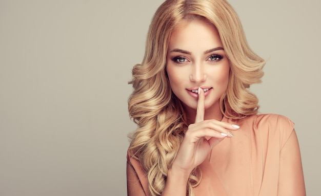Beautiful girl blonde hair with an elegant hairstyle  holding a finger to her mouth with a secret Premium Photo