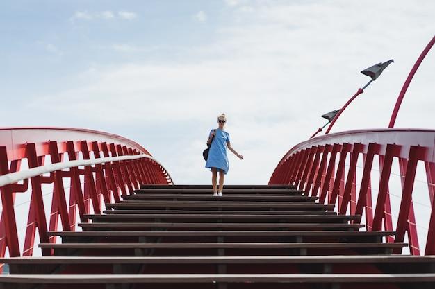Beautiful girl in a blue dress posing on the bridge Free Photo