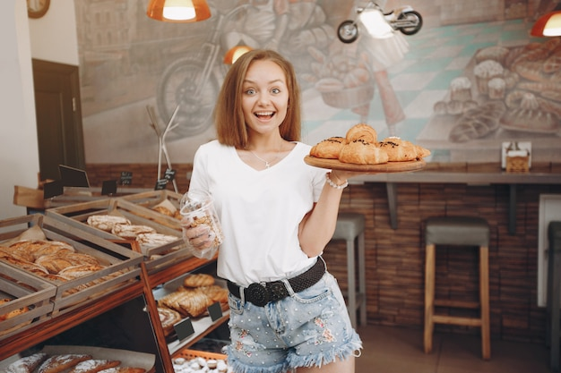 Beautiful girl buys buns at the bakery Free Photo