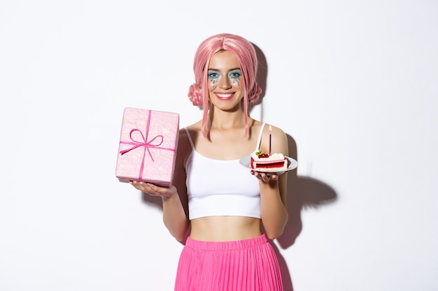 ピンクのかつらで誕生日を祝って、贈り物とb-dayケーキを持って、立っている美しい少女。 無料写真