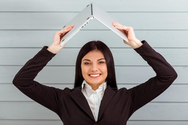 Beautiful girl in classical suit holding laptop overhead. Premium Photo