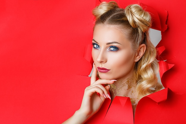 A beautiful girl in climbs out of a hole in red paper Premium Photo